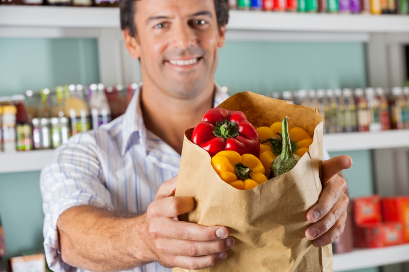 6499892-male-customer-showing-bellpeppers-in-paper-bag